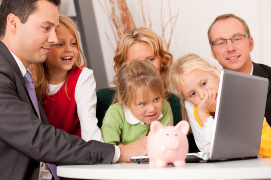 (assets, money or similar) doing some financial planning - symbolized by a piggy bank the daughter is holding in her hand
